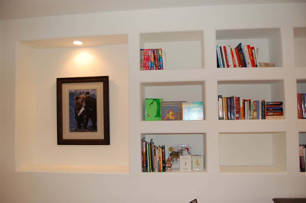 simple white basement book shelves and picture frame