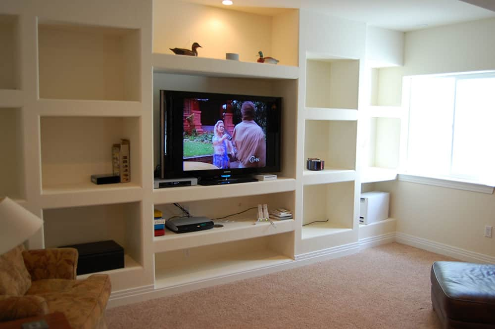 simple white basement tv built in tv frame and bookcases